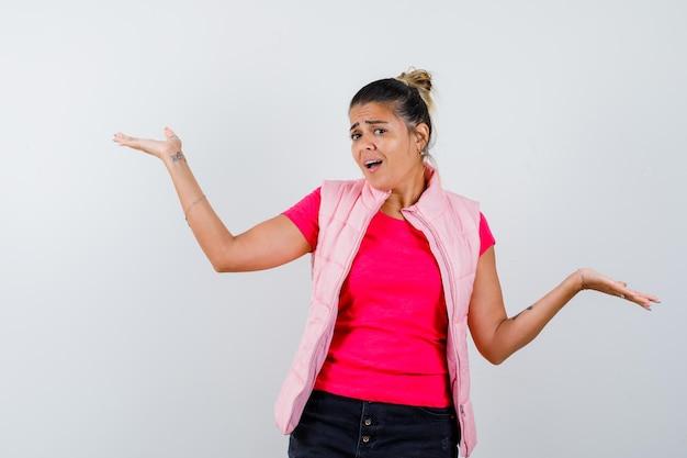 Kobieta robi powitalny gest w koszulce, kamizelce i wygląda na pewną siebie