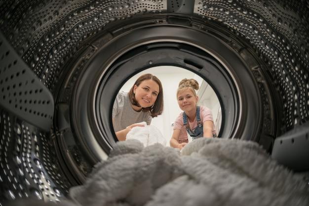 Kobieta robi pranie z córką osiągając ręcznik wewnątrz pralki, widok od wewnątrz