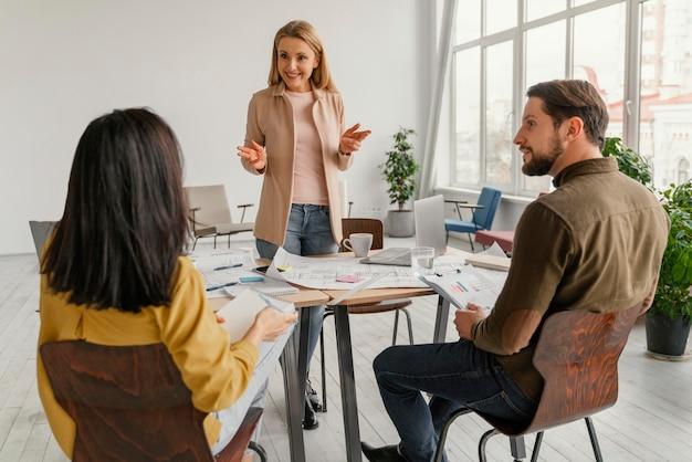 Kobieta robi prezentację przed kolegami