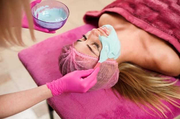 Kobieta robi procedurę w salonie piękności. maska alginianowa, czyszczenie ultradźwiękowe. pielęgnacja twarzy zabiegi kosmetologiczne bez operacji.