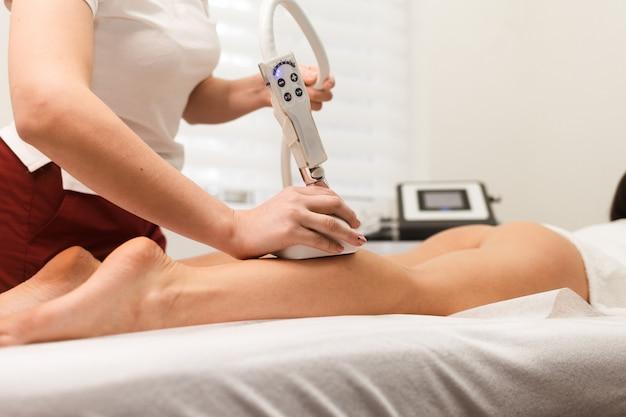 Kobieta robi próżniowy masaż antycellulitowy na nogach. urządzenie do masażu próżniowego