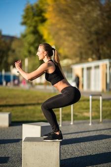 Kobieta robi przysiady i ćwiczy na świeżym powietrzu na ulicy