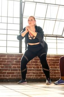 Kobieta robi przysiady na zajęciach fitness