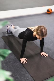 Kobieta robi push up na matę do ćwiczeń