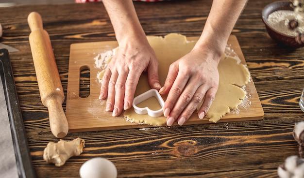 Kobieta robi pyszne domowe ciasteczka w kształcie serca w swojej kuchni