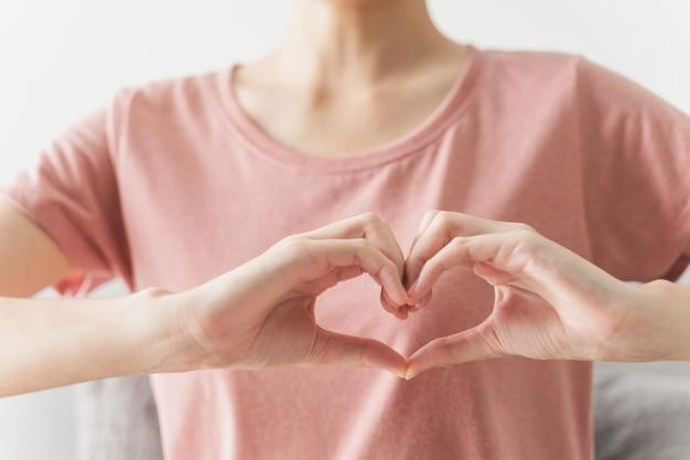 Kobieta robi ręce w kształcie serca miłość serce ubezpieczenie zdrowotne odpowiedzialność społeczna darowizna