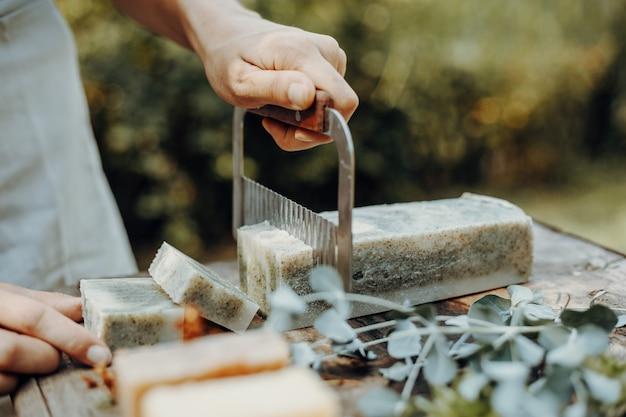 Kobieta robi ręcznie robione naturalne mydła na starym drewnianym stole