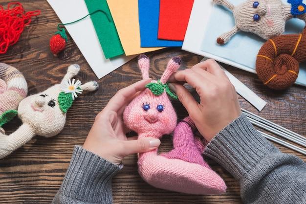 Kobieta robi ręcznie robione zabawki świąteczne z dzianiny