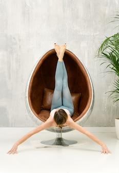 Kobieta robi rozciągającą pozycję jogi na skórzanym fotelu z wanną z wyciągniętymi rękami i uniesionymi nogami
