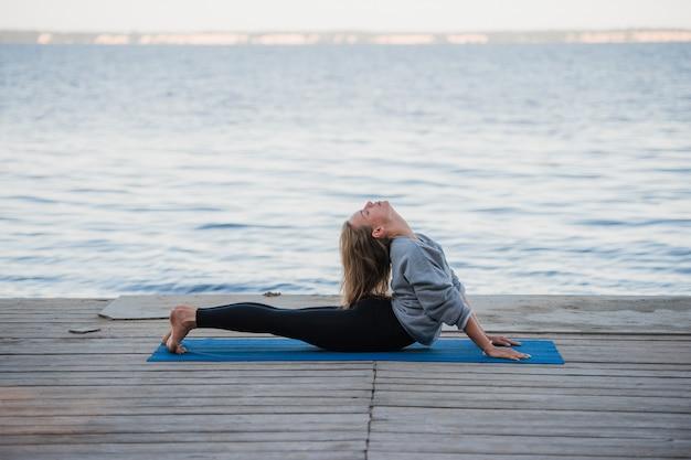 Kobieta robi rozciągające ćwiczenia jogi rano na molo w pobliżu morza lub jeziora