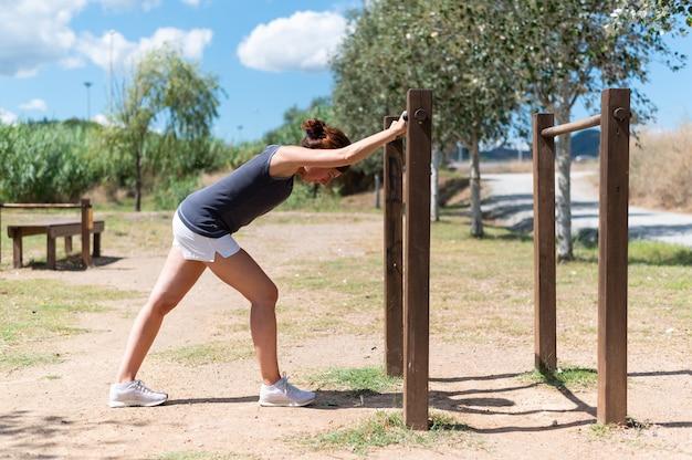 Kobieta robi rozciąganie na świeżym powietrzu w parku