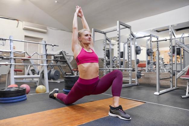 Kobieta robi rozciąganie treningu na siłowni, kobieta ćwiczy jogę