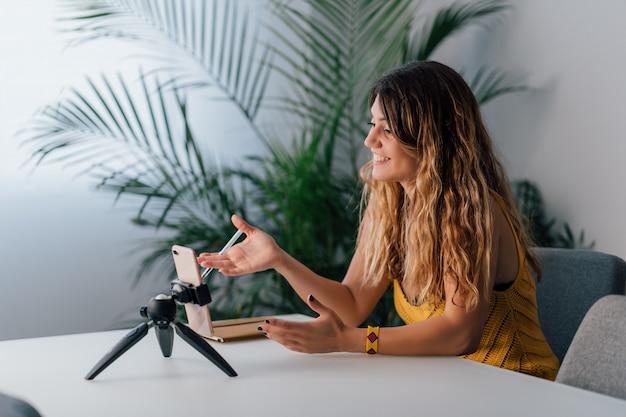 Kobieta robi rozmowie wideo z jej smartphone w domu.