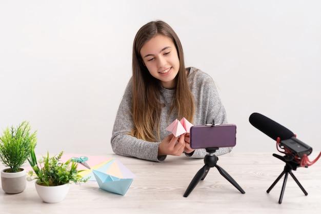 Kobieta robi samouczek na temat origami na blogu z kolorowymi kartkami, patrząc w kamerę, udostępniając je na żywo w sieciach społecznościowych za pośrednictwem internetu