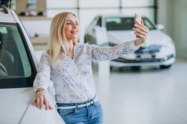 Kobieta robi selfie samochodem w salonie samochodowym