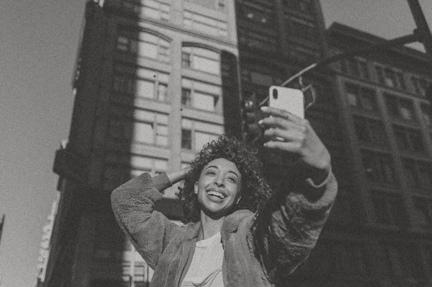 Kobieta robi selfie w mieście w tonacji czarno-białej