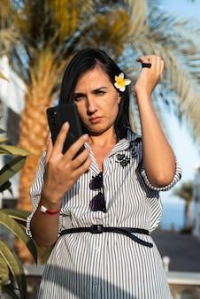 Kobieta robi selfie w pobliżu palmy
