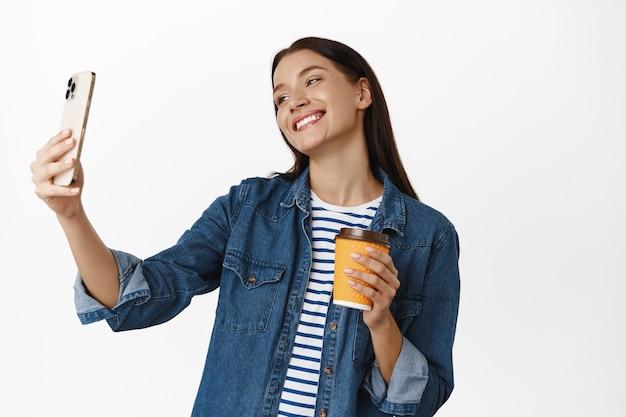 Kobieta robi selfie z filiżanką kawiarni na wynos uśmiechnięta szczęśliwy, relaksujący dzień, stojąc nad białymi