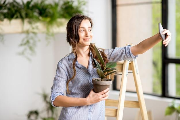 Kobieta robi selfie zdjęcie stojące z doniczką na drabinie w domu