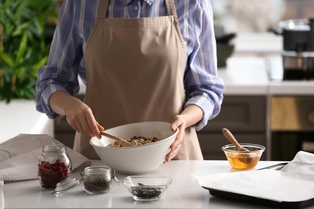 Kobieta robi smaczne batoniki muesli w kuchni