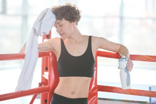 Kobieta robi sobie przerwę po ciężkim treningu. przygotowanie do zawodów bokserskich