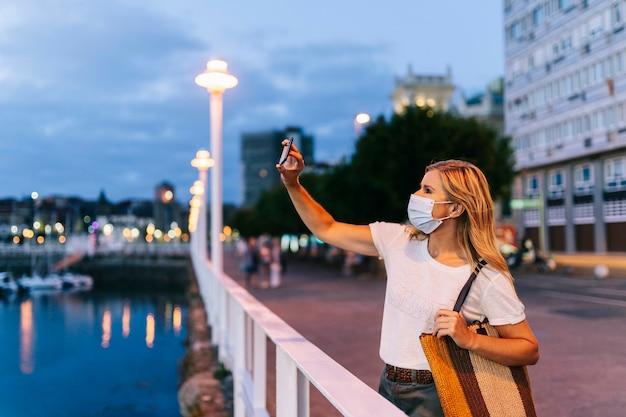 Kobieta robi sobie selfie na przystani w mieście asturias w gijon