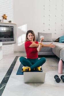 Kobieta robi sportom na macie po klasach online z laptopem w domu