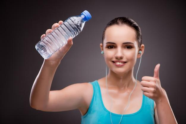 Kobieta robi sportowi z butelką świeża woda