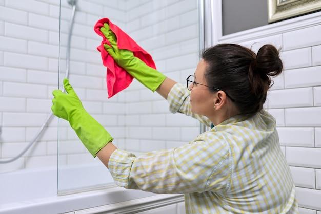 Kobieta robi sprzątanie w łazience, w domu. żeńskie mycie polerujące szkło prysznicowe z myjką z mikrofibry.