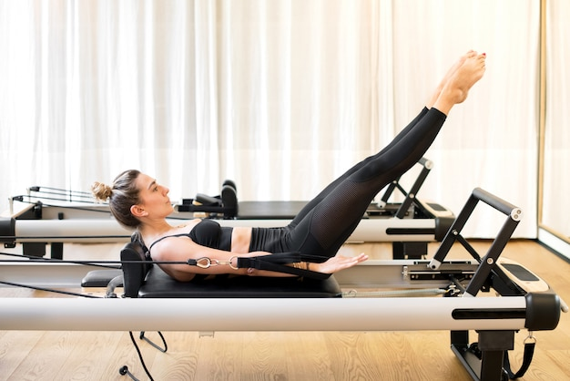 Kobieta robi sto ćwiczeń pilates na łóżku reformatora