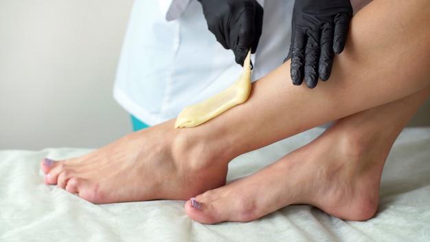 Kobieta robi stopie woskuje profesjonalną close-up pracę