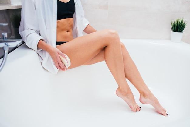 Kobieta robi suchemu masażowi z muśnięciem. dziewczyna w czarnej bieliźnie co peeling skóry w łazience. antycellulit, eksfoliacja, koncepcja pielęgnacji skóry. twarz nie jest widoczna.