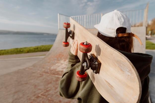 Kobieta robi sztuczki deskorolce nad jeziorem