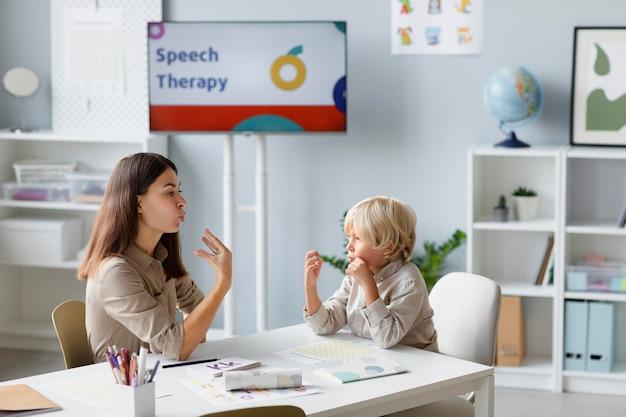Kobieta robi terapię mowy z małym blond chłopcem