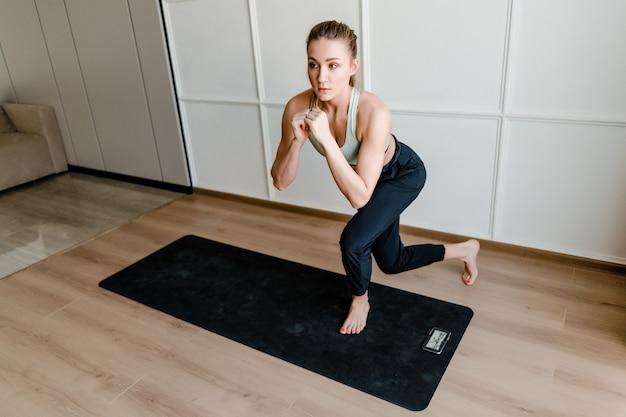 Kobieta robi treningu sportowego, patrząc na telefon z treningu online na żywo