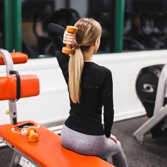 Kobieta robi triceps ćwiczeniu z dumbbell