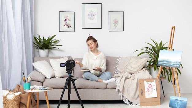 Kobieta robi vlog w domu z jej aparatem
