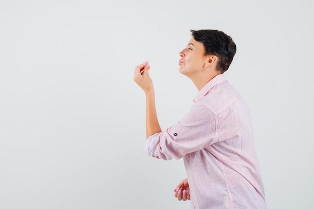 Kobieta robi włoski gest, niezadowolona z głupiego pytania w różowej koszuli.