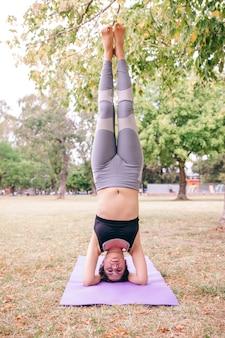 Kobieta robi wspieranej headstand joga stanowi na zewnątrz. pilates zdrowy styl życia dla ludzi do ćwiczeń jogi. trening na świeżym powietrzu i utrzymanie formy. ludzie robią medytację dobrego samopoczucia w parku.