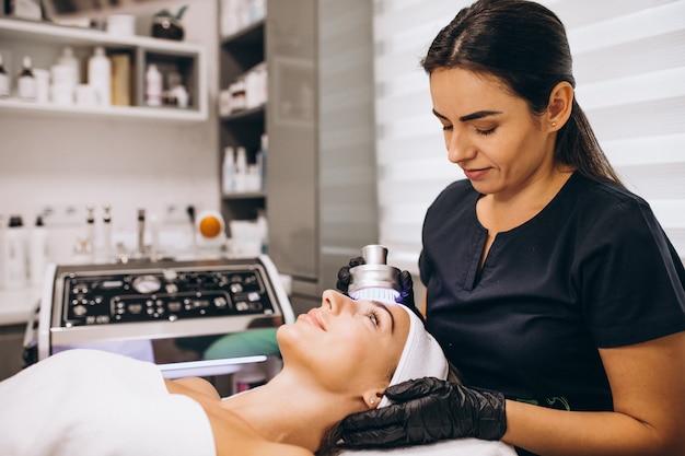 Kobieta robi zabiegi kosmetyczne w salonie piękności