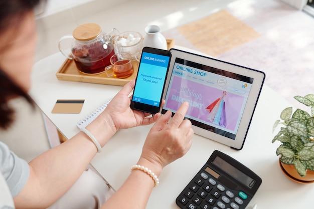 Kobieta robi zakupy online i płaci za zakupy za pomocą aplikacji bankowej na smartfonie