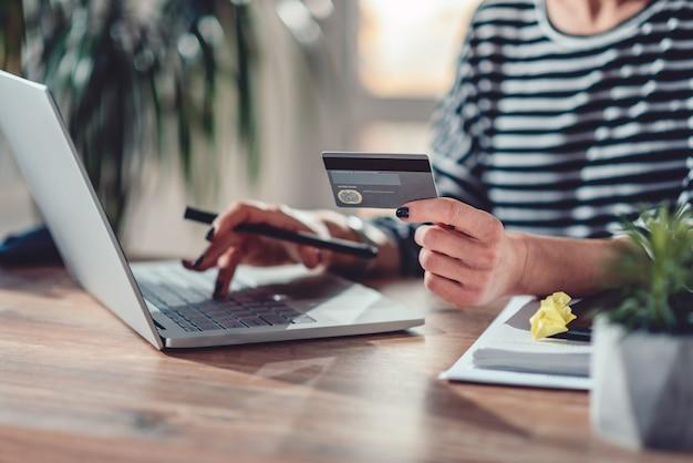 Kobieta robi zakupy online i używa karty kredytowej