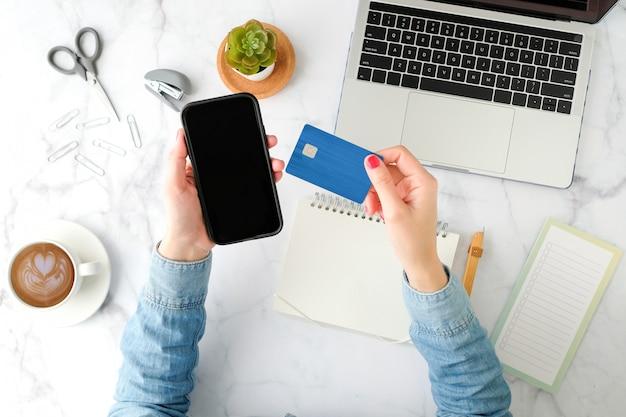 Kobieta robi zakupy online w aplikacji na telefon komórkowy z niebieską kartą kredytową. płaski i nowoczesny styl.