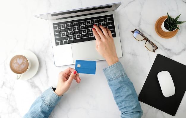 Kobieta robi zakupy online z błękitną kartą kredytową. płaski i nowoczesny styl.