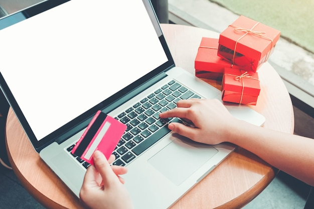 Kobieta robi zakupy online z kartą debetową w kawiarni z laptopem