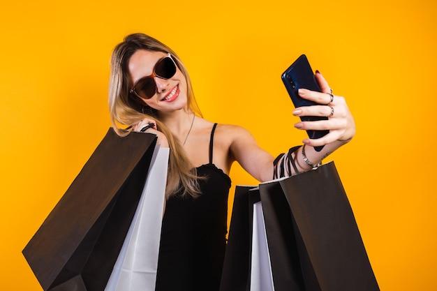 Kobieta robi zakupy przy selfie z torby na zakupy na żółtym tle.