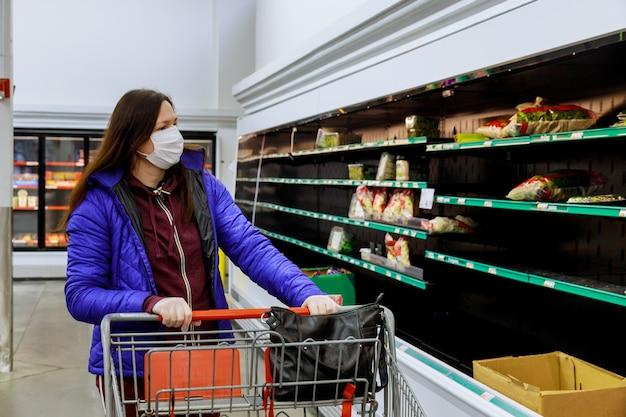 Kobieta robi zakupy przy supermarketem z ochrony twarzy maską i rękawiczkami.
