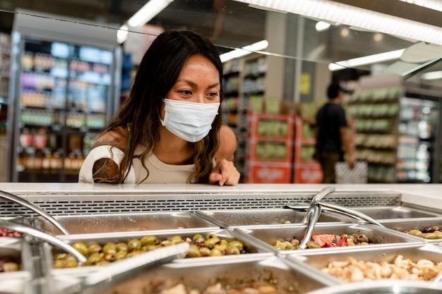 Kobieta robi zakupy spożywcze, sekcja delikatesów w supermarkecie podczas nowej normy