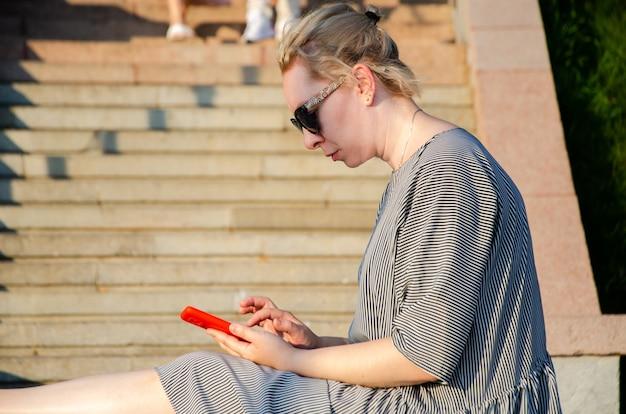 Kobieta robi zakupy w internecie lub komunikuje się w komunikatorach ze smartfona w parku