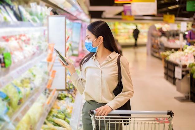 Kobieta robi zakupy w supermarkecie z maską